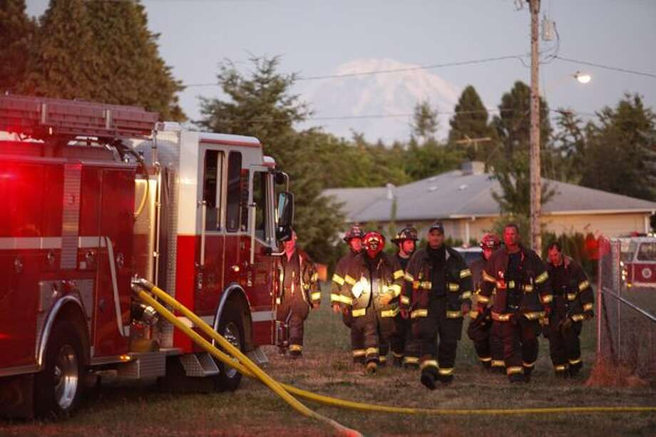 Firefighters walk back to their truck during a four-alarm fire at a Renton Highlands apartment complex Tuesday evening. Photo: Clifford DesPeaux, Seattlepi.com