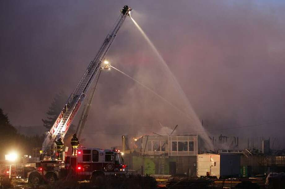 Firefighters spray water from above during a four-alarm fire at a Renton Highlands apartment complex Tuesday evening. Photo: Clifford DesPeaux, Seattlepi.com