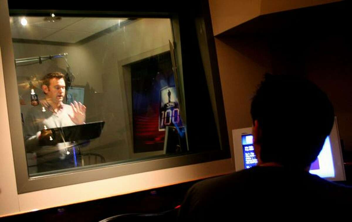Host Chris Cashman performs in the sound booth as lead producer Oren Stambouli looks on during Tuesday's live production of