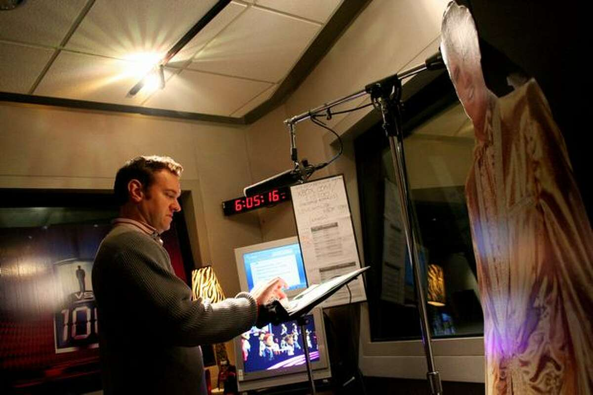 A cardboard cut-out of Elvis watches over host Chris Cashman as he performs in a sound booth Tuesday at Microsoft Studios.