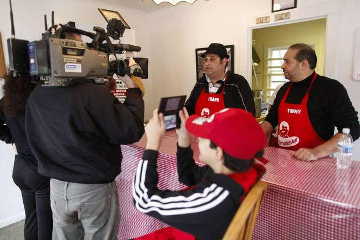 Sonny Rizzo takes a photo of reporters interviewing his father, Frank, at Rizzo's French Dip in Crown Hill.