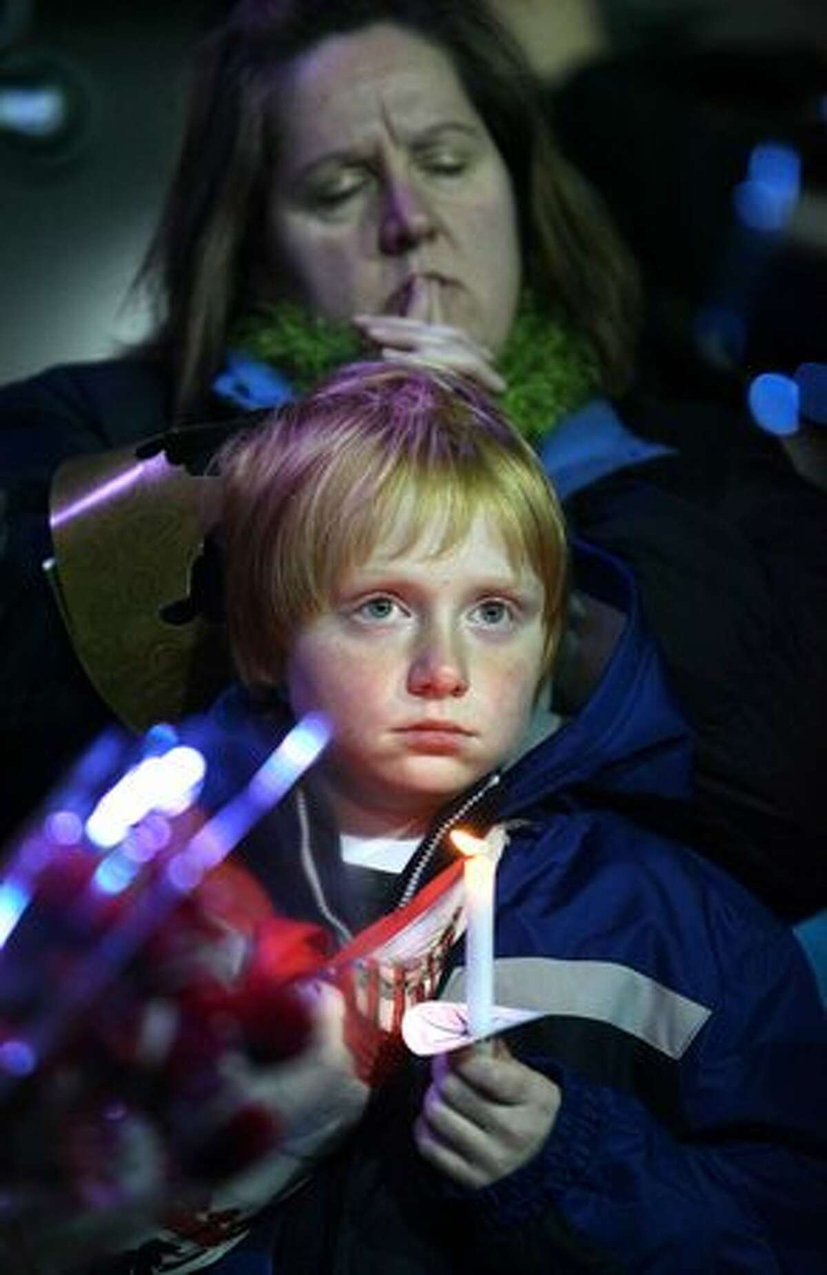 Kelly Groenwold and her son Aaron, of Lakewood, Wash., participate during a candlelight vigil on Wednesday December 2, 2009 at the Lakewood Family YMCA in Lakewood, Wash. Thousands gathered to pay their respects to four Lakewood Police officers who were shot and killed at a coffeepot Sunday morning in Parkwood.