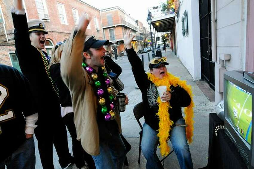 (L-R) New Orleans Saints fans Raoul Duke, Jesse Brunet and Chrissie Brunet watch the Saints play against the Indianapolis Colts during Super Bowl XLIV on the sidewalk in the French Quarter in New Orleans on Sunday, Feb. 7, 2010.