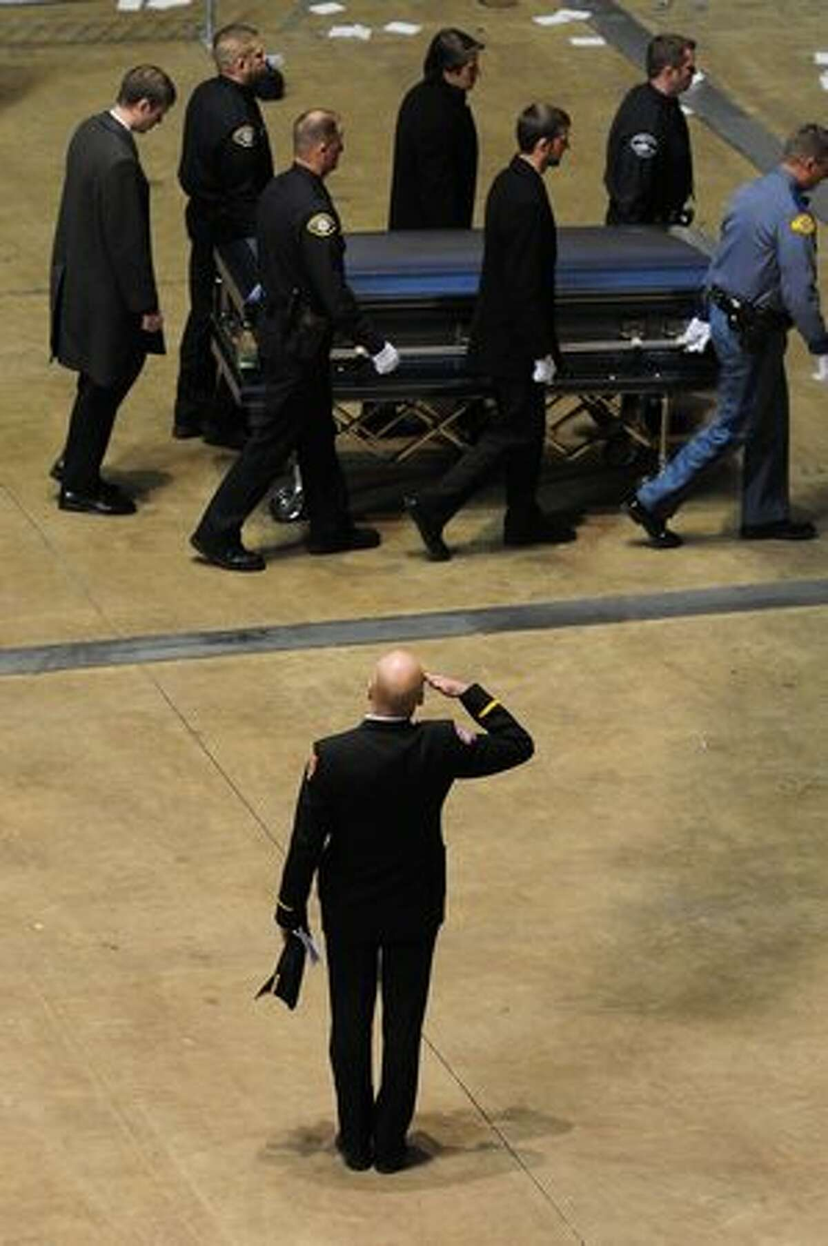 An officer salutes as a casket is removed following a memorial service for four slain police officers in Tacoma.