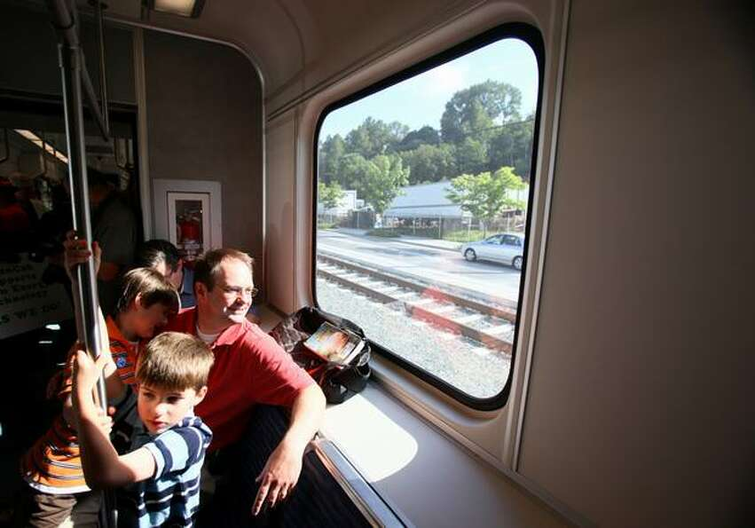 Daniel Triplett, foreground, enjoys his time on a new Link light rail car as his dad, King County Ex