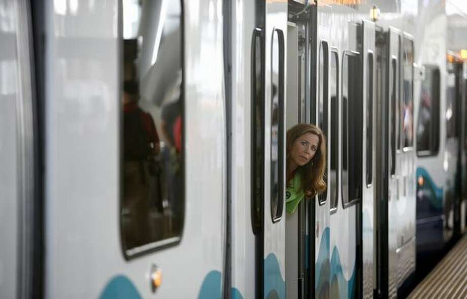 A passenger pokes her head out of a light rail car during the kickoff of service on Saturday July 18, 2009. Sound Transit's new Link light rail began service between Westlake Center and Tukwila. Photo: Joshua Trujillo, Seattlepi.com