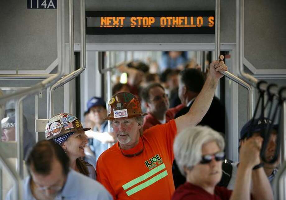 Passengers, including Lloyd Lee, center, ride Link light rail during the kickoff of service on Saturday July 18, 2009. Photo: Joshua Trujillo, Seattlepi.com