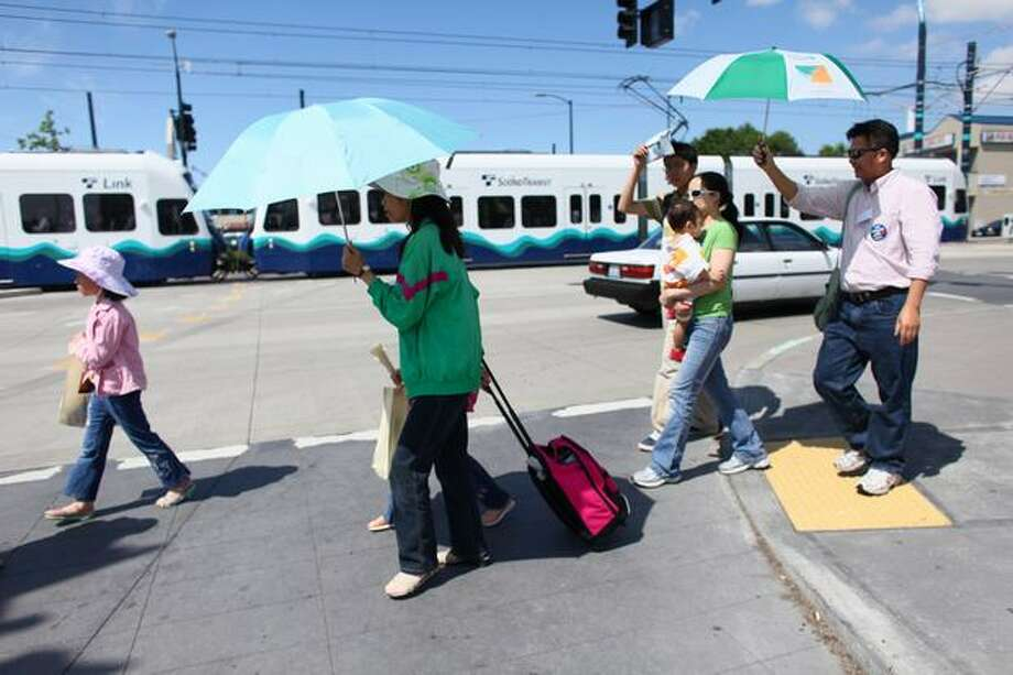 Passengers prepare to board a Link light rail train on Martin Luther King Jr. Way South during the kickoff of service on Saturday July 18, 2009. Sound Transit's new Link light rail began service between Westlake Center and Tukwila. Photo: Joshua Trujillo, Seattlepi.com