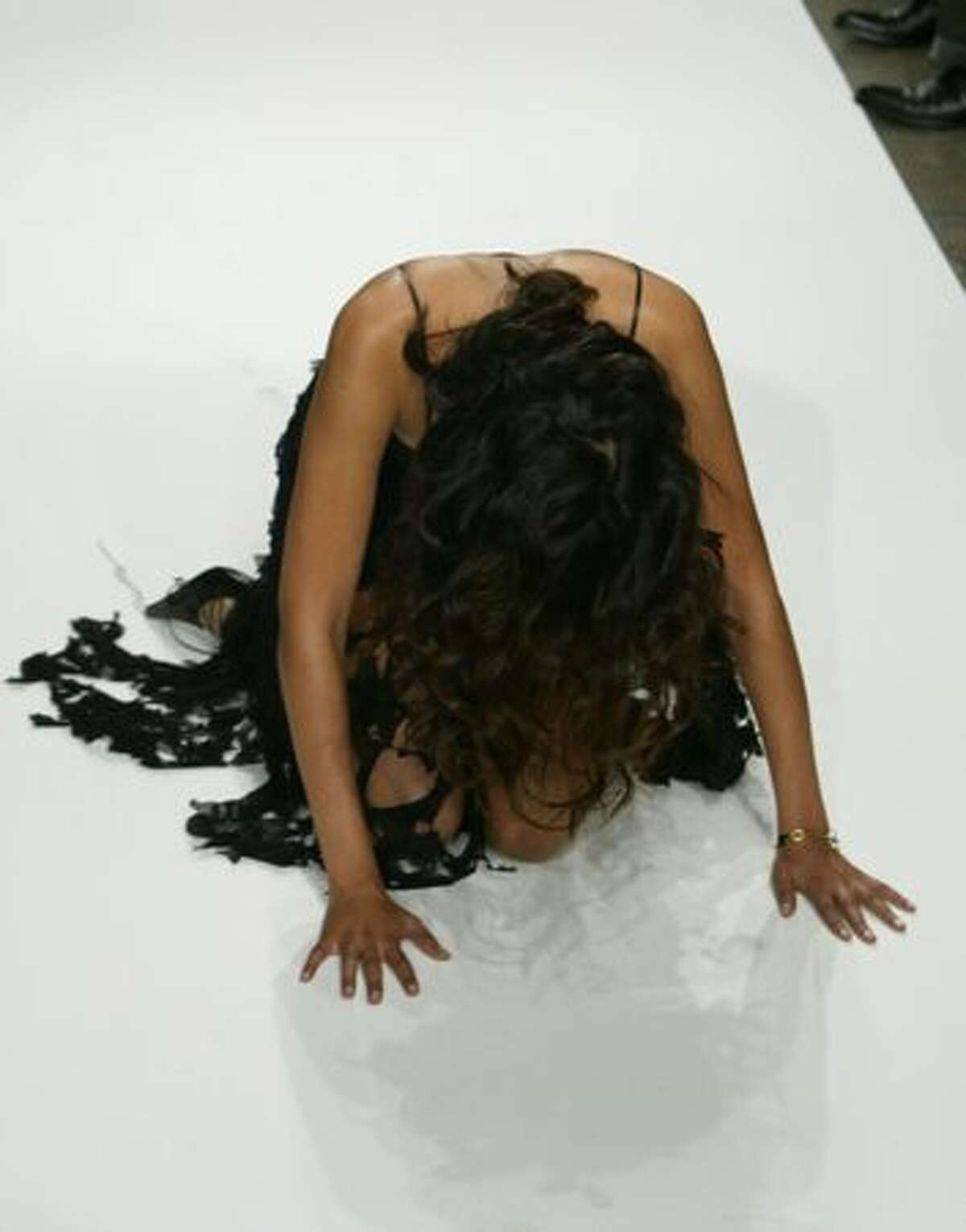 A model kneels after falling down as she was walking the runway at the Maggie Barry Collection Spring 2005 show at the Mercedes-Benz Fashion Week at Smashbox Studios on October 27, 2004 in Culver City, California.