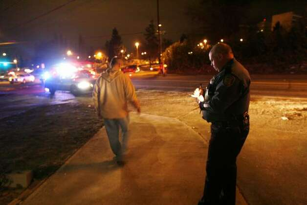 Seattle Police officer Eric Michl of the department's DUI squad gives a  field test to Rodney James, who was drunk on Dec. 12, 2009, when he  plowed into a Beacon Hill family returning from vacation. Photo: Casey McNerthney, Seattlepi.com
