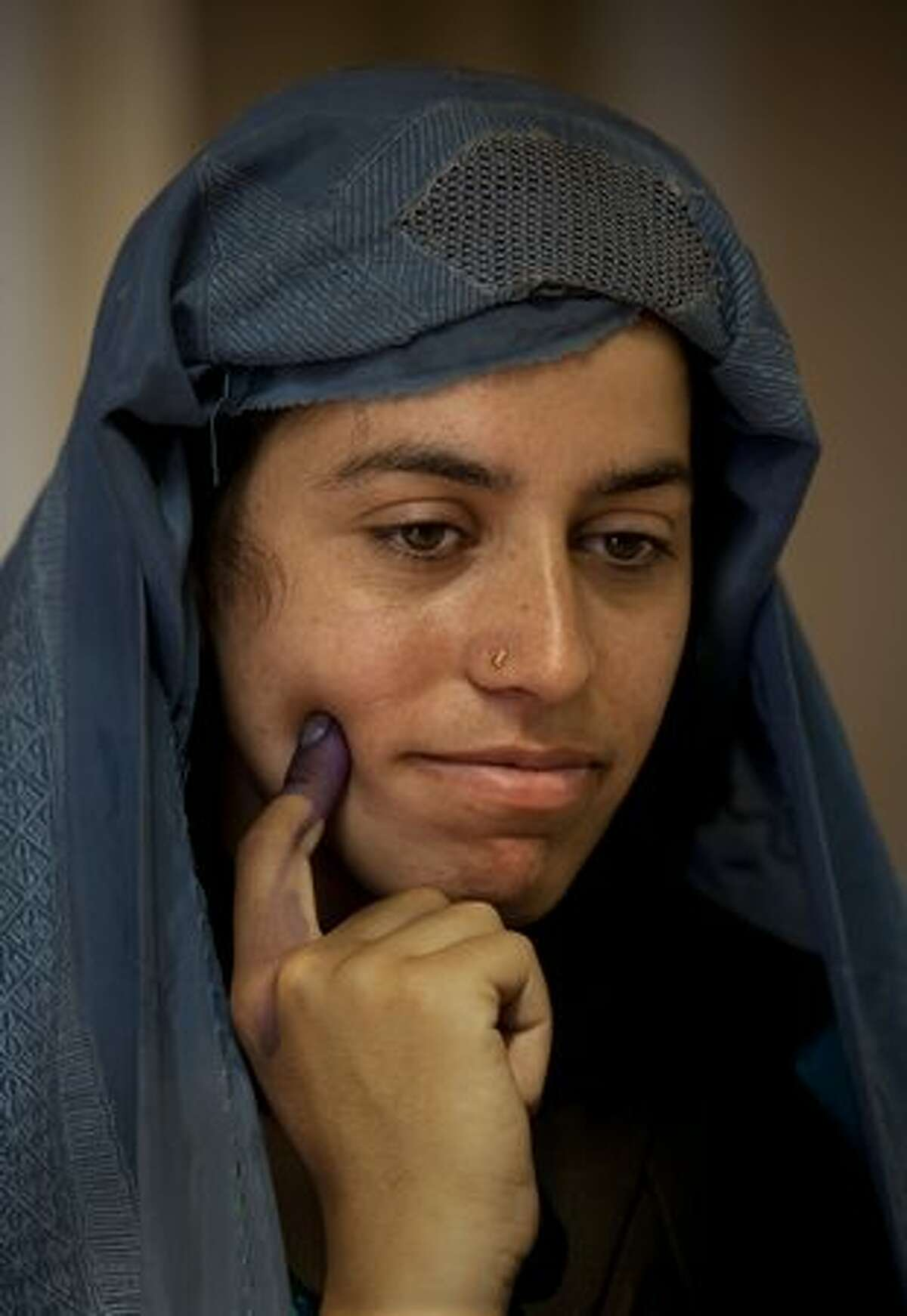 An Afghan woman waits for a friend after voting with her inked finger at a polling station on Aug. 20 in Kabul, Afghanistan.