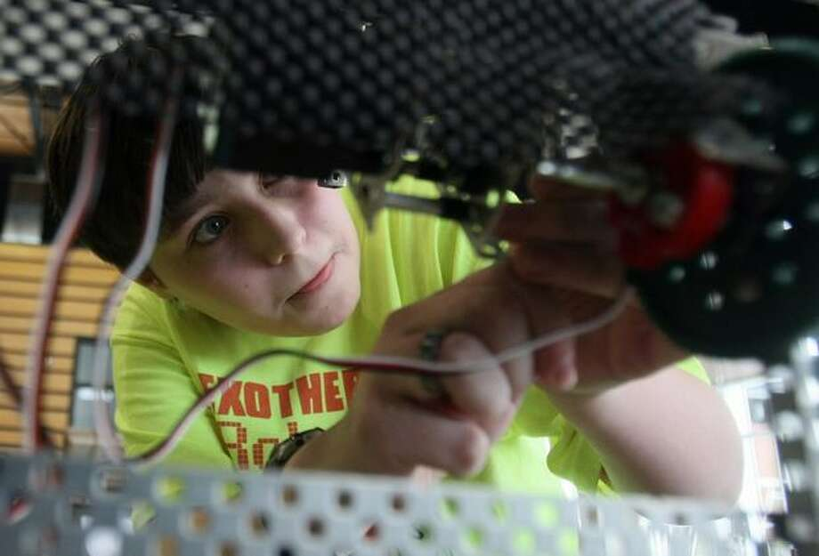 David Lovett, 13, a member of the Exothermic Robotics Club, works on a robot he helped design and build during the Washington State VEX Robotics Competition at Redmond High School on Saturday Feb. 27, 2010. Photo: Thom Weinstein, Special To Seattlepi.com