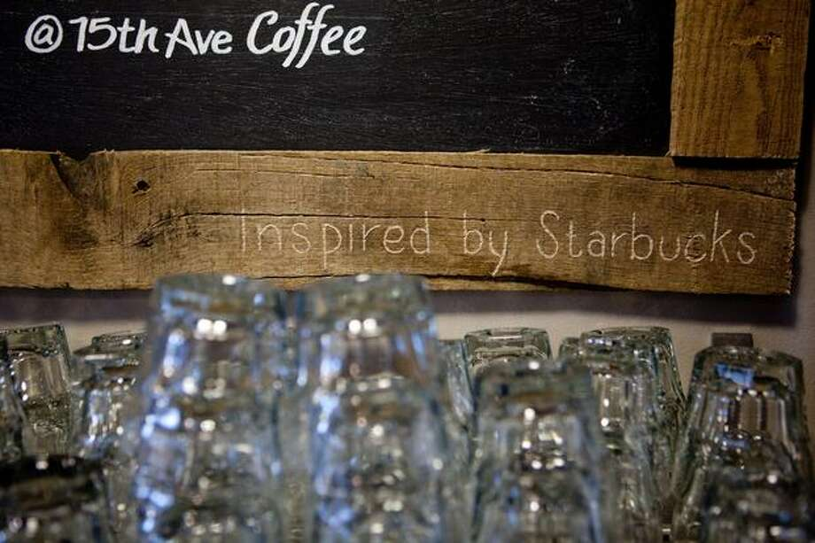 Starbucks' name is carved into the wooden frame of a menu board -- one of the few places it appears at the new 15th Avenue Coffee & Tea in Seattle's Capitol Hill neighborhood. Photo: Joshua Trujillo, Seattlepi.com