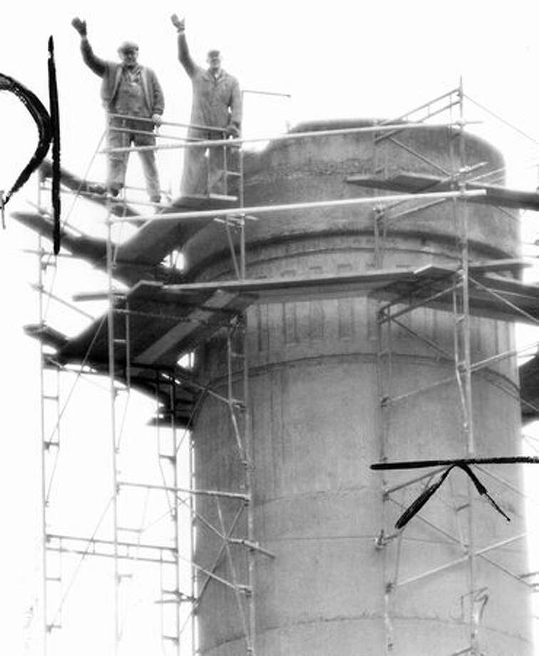 Leo McKay, left, and Howard Yeomans atop 160 foot concrete stack being demolished at Rainier Ice and Cold Storage Company, February 1959. Photo: P-I File