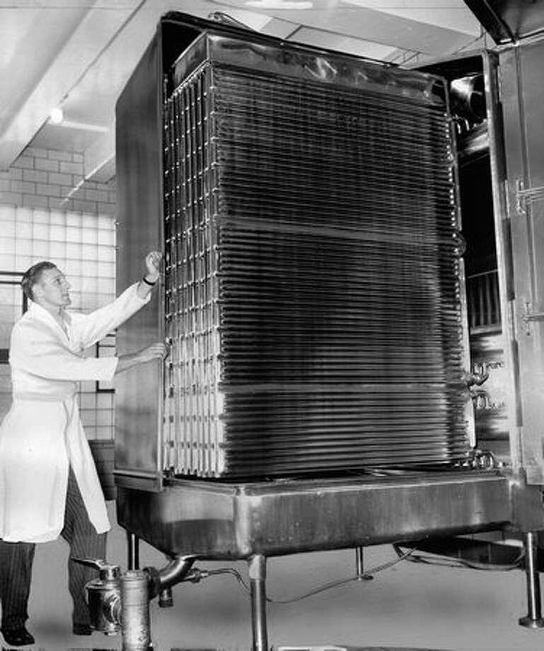 The August 1949 photo caption read: Stainless steel beer cooler chills Rainier Beer from 190 degrees to 45 degrees. The machine cools 150 gallons per minute. Photo: P-I File