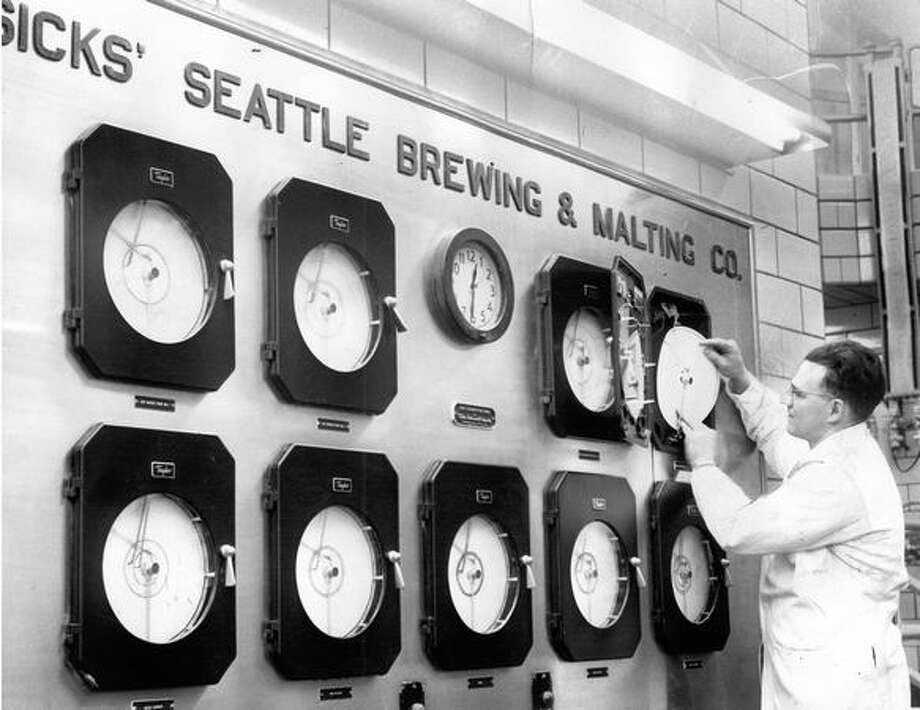 Verne Raught writes the history of every brew providing a check on each brew for future reference. August 1949. Photo: P-I File