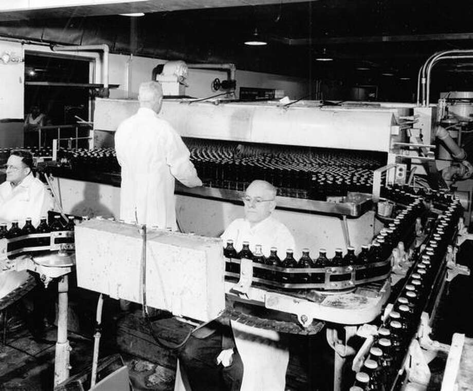 One-half million bottles of Rainier go through the bottling plant with military percision per day. August 1949 Photo: P-I File