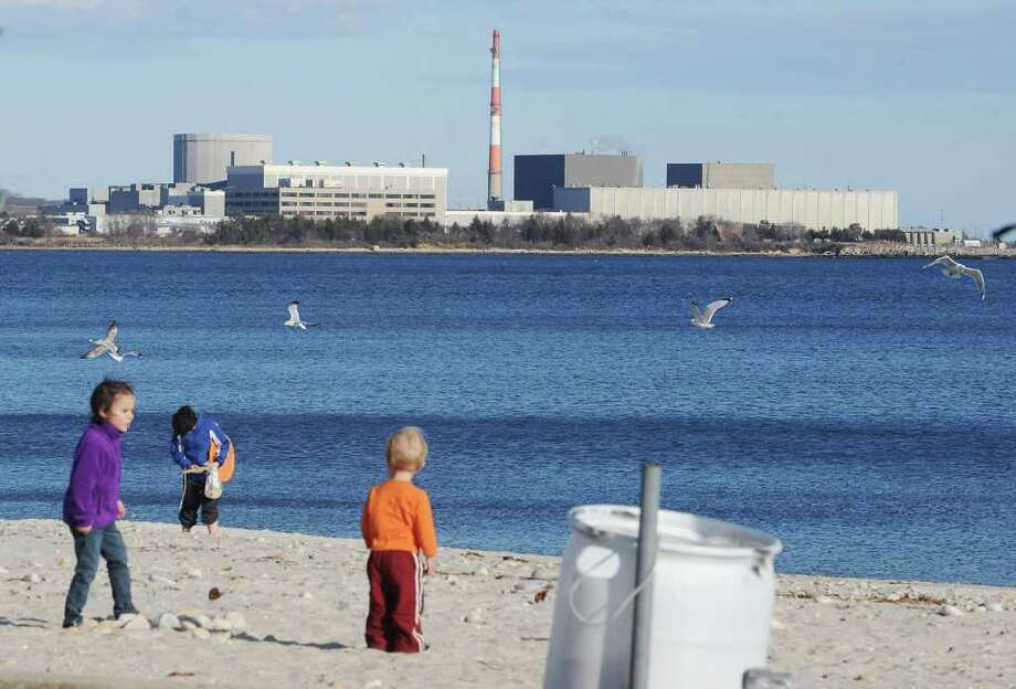 Families play on the beach with the Millstone Nuclear Power Plant in the background in Niantic, Conn. on Sunday March 20, 2011. Photo: Kathleen O'Rourke / Stamford Advocate