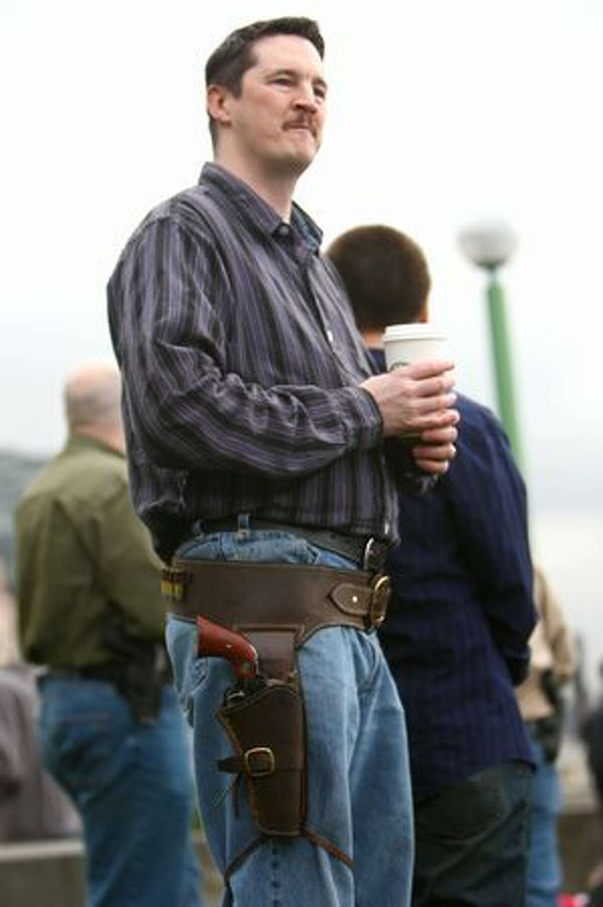Shannon Dunne drinks a Starbucks coffee while wearing his Ruger Vaquero 45 Colt during a press event at Victor Steinbrueck Park. Washington CeaseFire, the Brady Campaign to Prevent Gun Violence, and Washington State Million Mom March hope to pressure the chain into adopting a no-guns policy in all its stores.