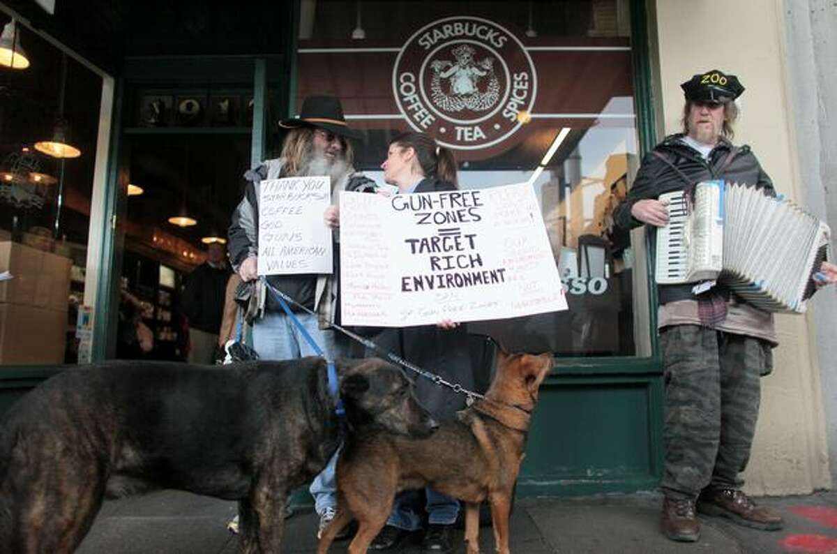 Brick Loomis, left, and Elisa Delaurenti hold signs outside the first Starbucks store, at Seattle's Pike Place Market, opposing a movement to pressure the coffee chain into banning guns from all its stores.