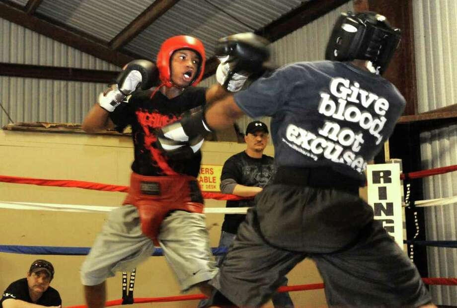 West Orange-Stark's basketball player, O'Shanique Foster (left) spars with Chad Broussard (right) at King's Gym in Orange, Thursday.  O'Shanique is the top seed of eight boxers in his weight class for the U.S. Olympic Trials. Tammy McKinley/The Enterprise Photo: TAMMY MCKINLEY / Beaumont