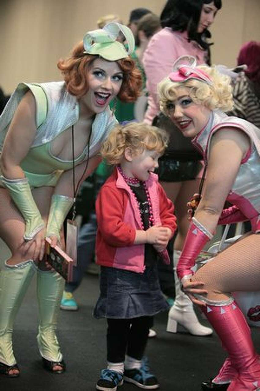 Baylyn Savage, 2, poses with members of the Atomic Bombshells during Emerald City ComiCon.