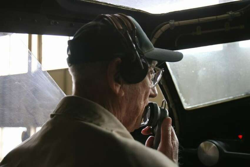 Retired U.S. Army Air Forces pilot Hank Hendrickson sits in the familiar flight deck of a Boeing B-17 Flying Fortress bomber, talking via radio with retired pilot Walter Sherrell, who was in a Boeing B-29 Superfortress.
