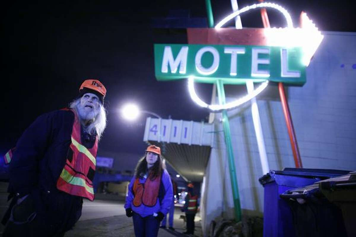John Coelho, left, and Teresa Addison Coe, members of FAWN (Fremont and Wallingford Neighbors) watch a steady stream of suspicious looking people entering and exiting a motel on Aurora Avenue on Wednesday Jan. 28. They're standing in front of the Italia and Isabella motels, both owned by Dean and Jill Inman.