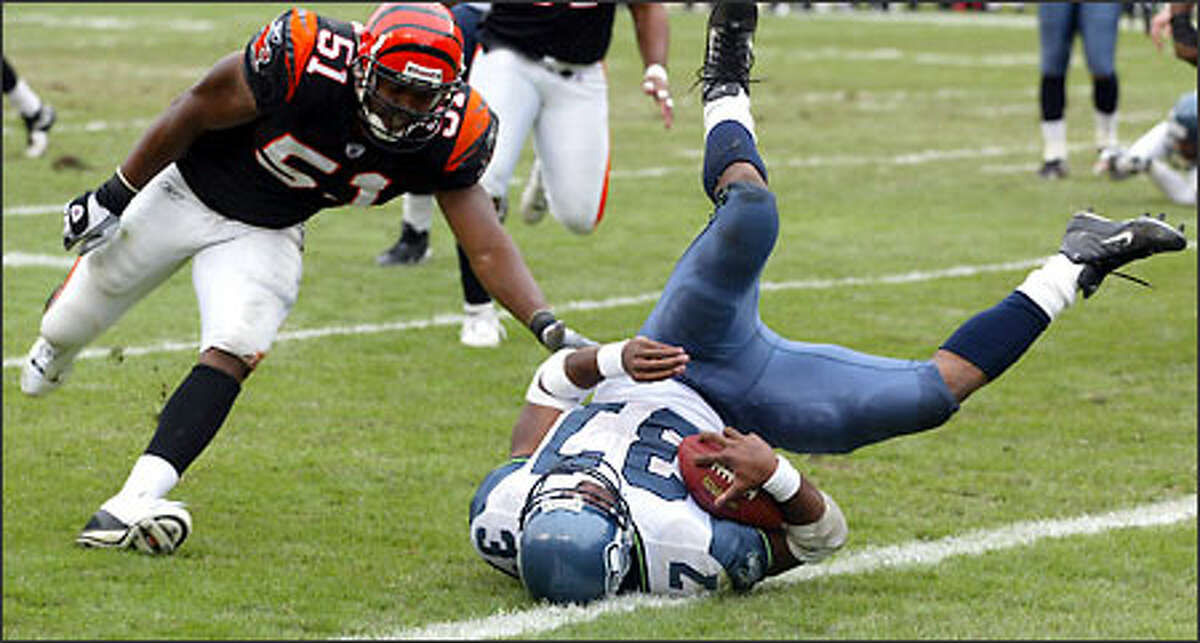 Shaun Alexander tumbles into the end zone past Bengals linebacker Kevin Hardy, scoring on a 2-yard pass from Matt Hasselbeck. Josh Brown's PAT made it 14-14. Alexander gained 57 yards on the scoring drive.