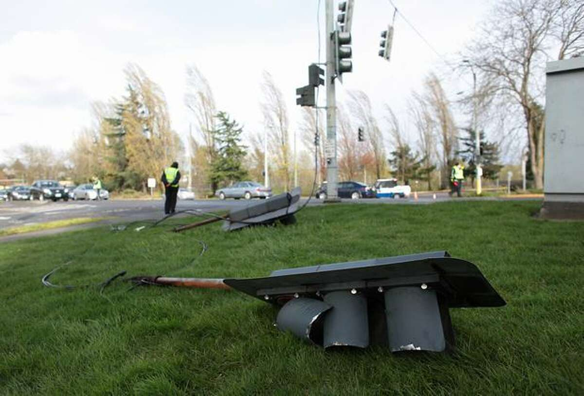 A traffic control light rests on the side of the road after falling into the intersection of Northeast 44th Street and Montlake Boulevard Northeast during a strong windstorm on Friday April 2, 2010. Power was knocked out to thousands of homes and businesses across the region because of the high winds.