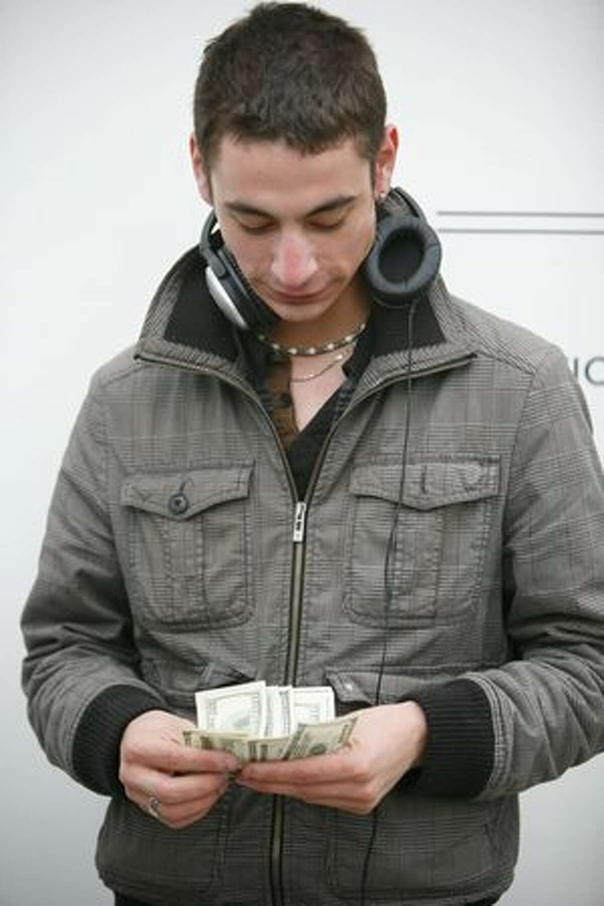 Quentin Laudrain counts his money before making a purchase of Apple's new iPad during the release of the device at the University Village Apple Store in Seattle.