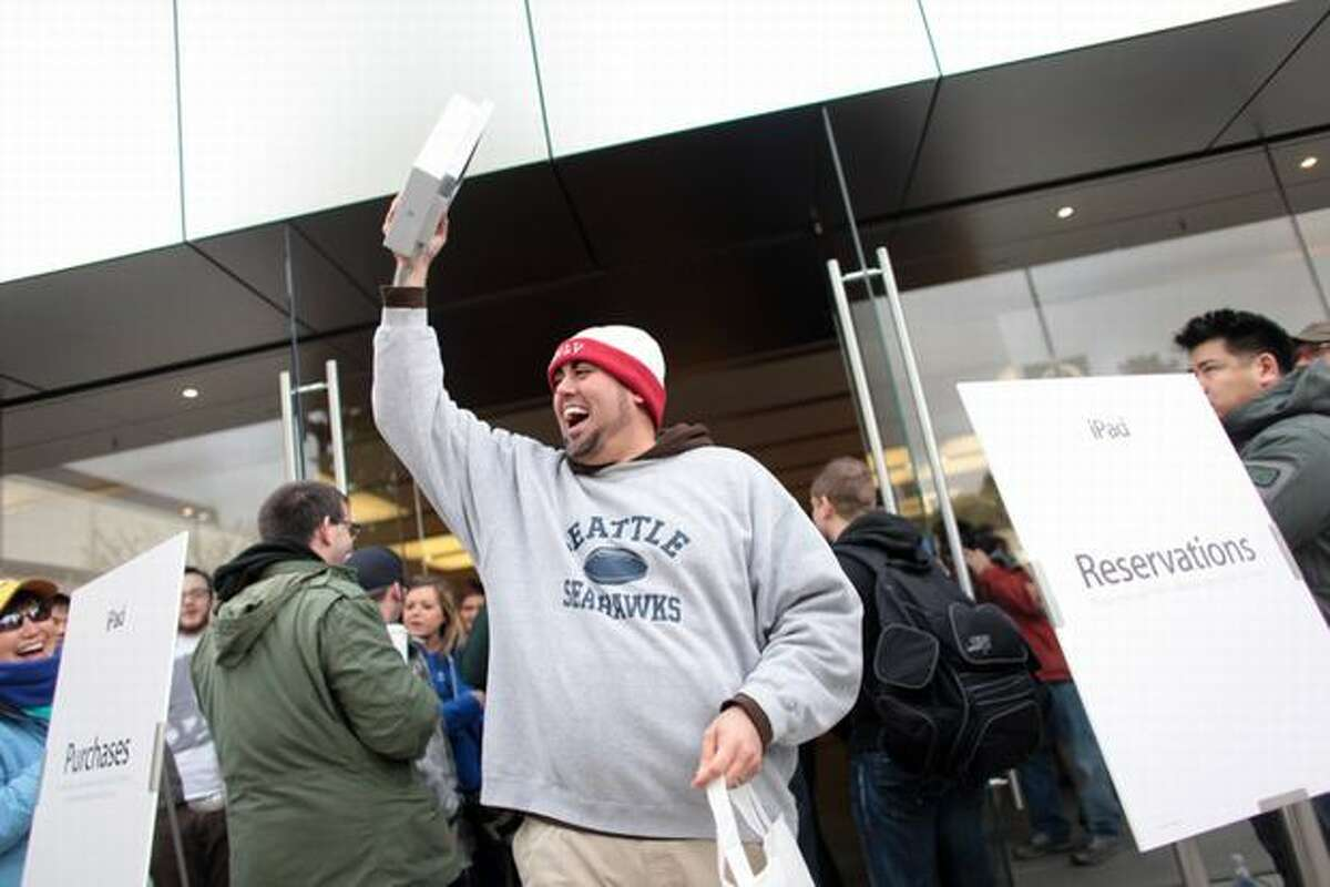 John Knight of Seattle emerges from the Apple Store after being the first customer to purchase an iPad during the release of Apple's much-hyped new device at the University Village Apple Store in Seattle. Knight waited all night with a (paper) book, a couple blankets and a folding chair.