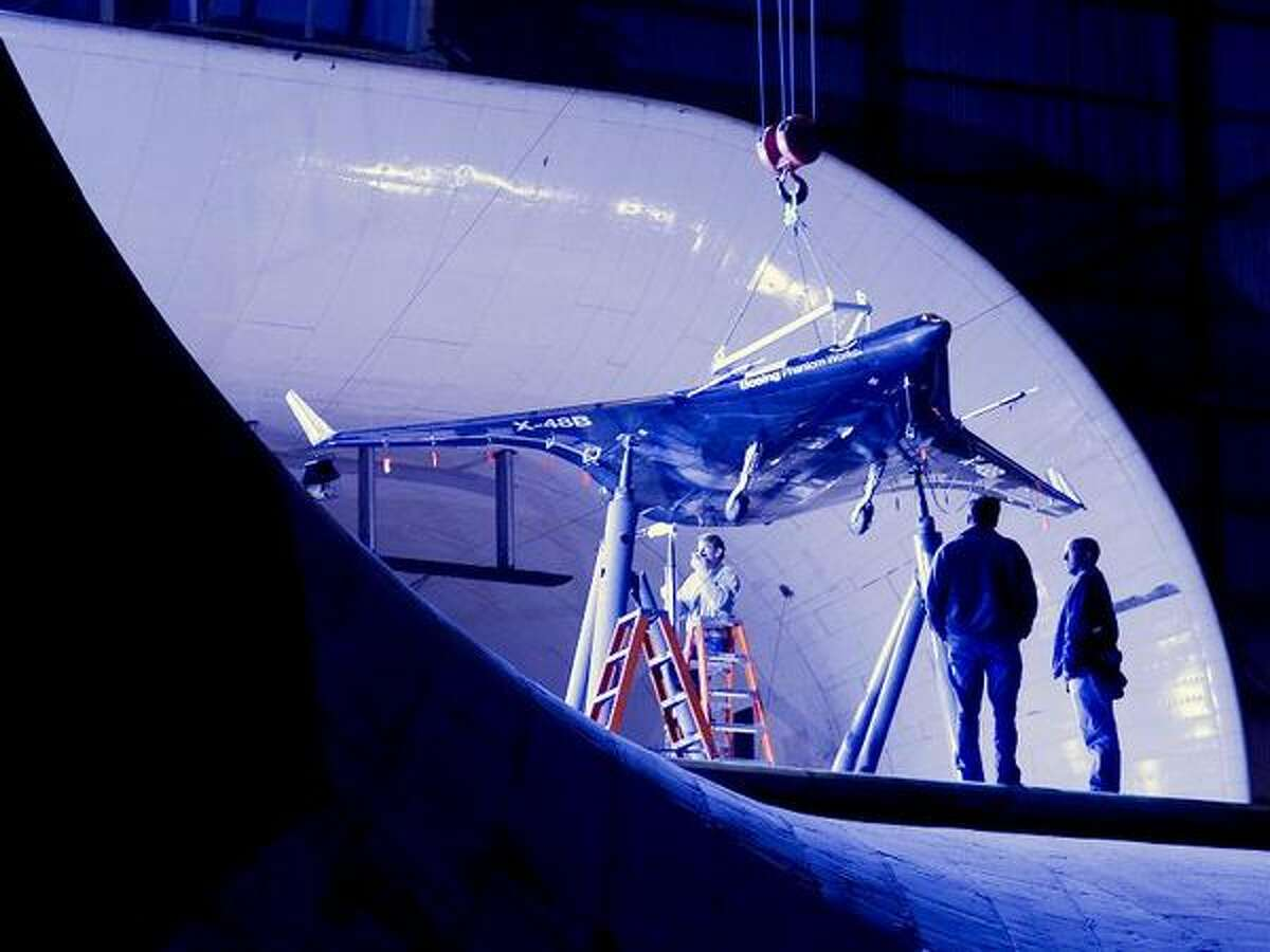 Researchers at NASA's Langley Research Center in Hampton, Va., test the a 21-foot wingspan 8.5 percent scale prototype of a blended wing body aircraft in Langley's historic full-scale wind tunnel in May 2006. Boeing Phantom Works has partnered with NASA and the Air Force Research Laboratory to study the structural, aerodynamic and operational advantages of the advanced aircraft concept, a cross between a conventional plane and a flying wing design. (Boeing)