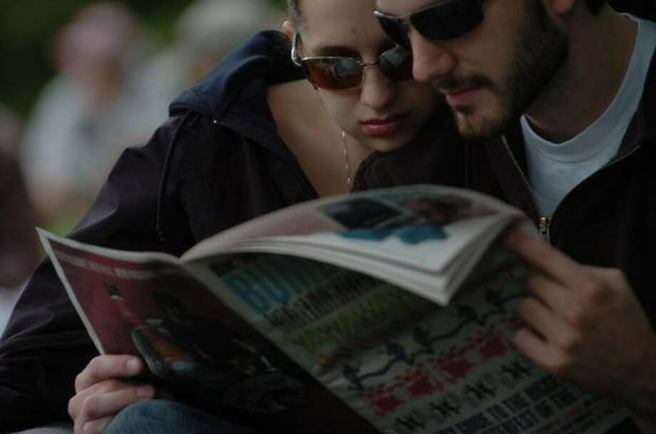 A couple read through a newspaper guide during day 1 of Bumbershoot Saturday in Seattle. Photo: Daniel Berman, Seattlepi.com
