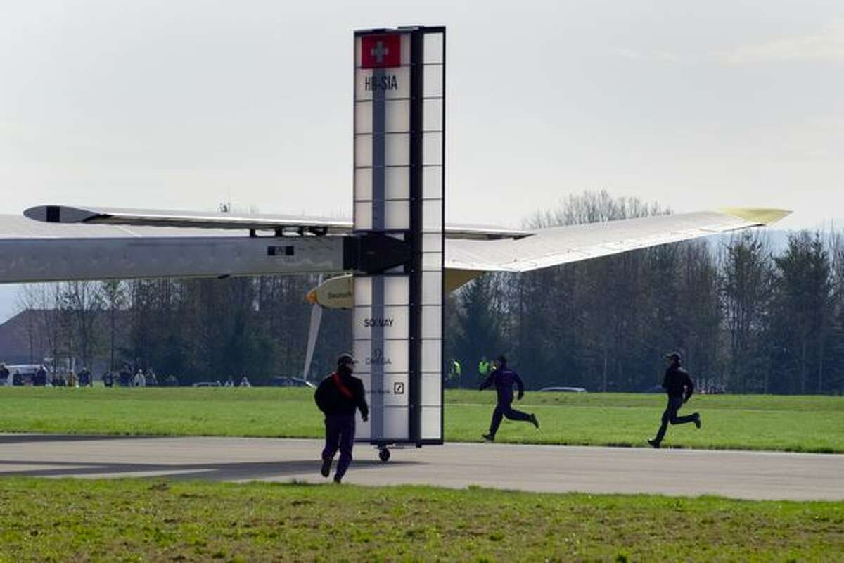 Staffers run behind the tail of the Solar Impulse aircraft, a pioneering Swiss bid to fly around the world on solar energy, takes off on its first test flight on April 7, 2010 from Payerne's air base, western Switzerland.