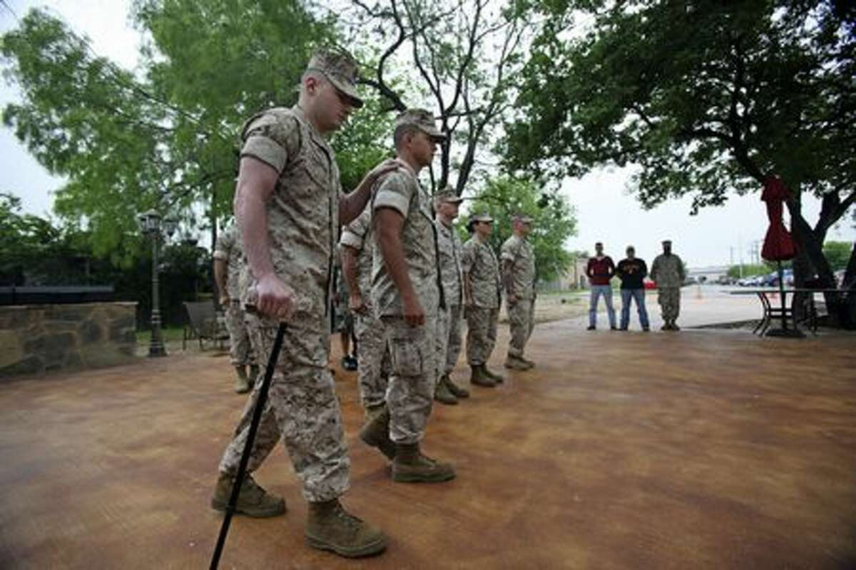 Cpl. Matthew Bradford leans on Marine Sgt. Johnathan Reyna as he steps forward to re-enlist.