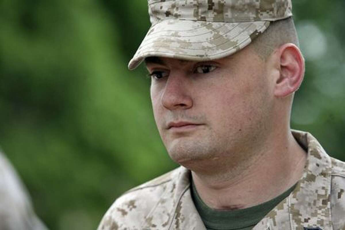 Cpl. Matthew Bradford listens to proceedings at his re-enlistment ceremony. He had made up his mind that he was going to deploy as many times as the Marines wanted him to when he was hurt a few months into his first tour of Iraq.