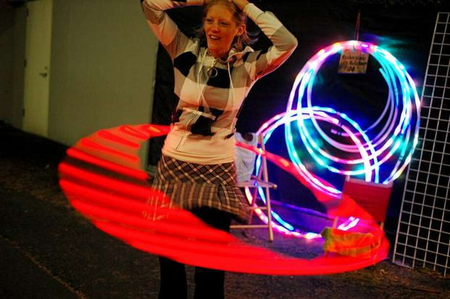 Michelle Purvis of My Art Maker demonstrates her rechargeable LED hula hoops outside of KeyArena near the end of day 2 of Bumbershoot. Photo: Daniel Berman, Seattlepi.com