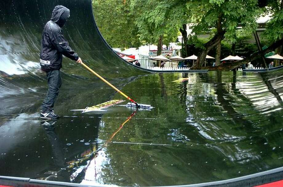 A man works on the Rockstar Energy Vert Ramp after morning rains on Monday. Photo: Daniel Berman, Seattlepi.com