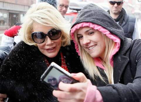 Actress Joan Rivers (left) has her picture taken with a fan on the street. Photo: Getty Images
