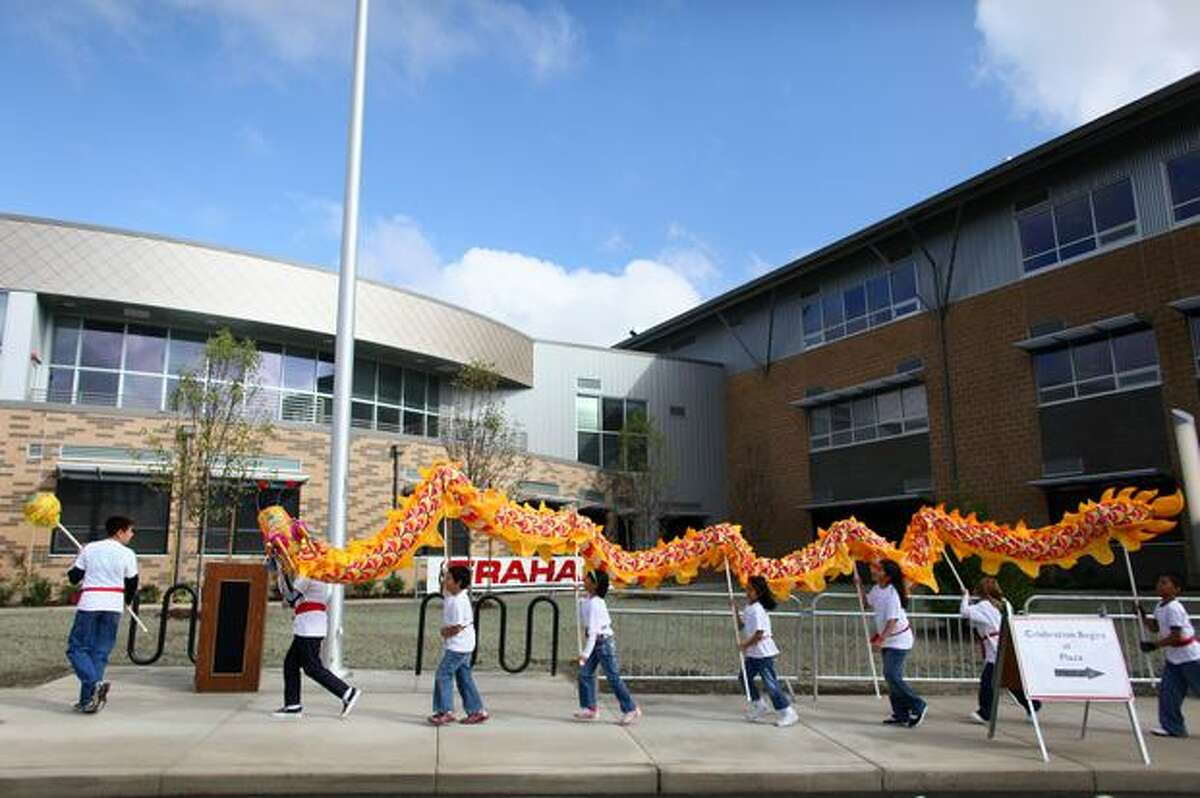 School children perform a dragon dance Tuesday in front of the new South Shore School on South Henderson Street in Seattle. Students, staff and community members participated in an opening ceremony for the school, which will open its doors to pre-kindergarten through seventh-grade students. The school will add eighth grade next year. The new $69.9 million school was built as part of a bond construction program voters approved in 2007.