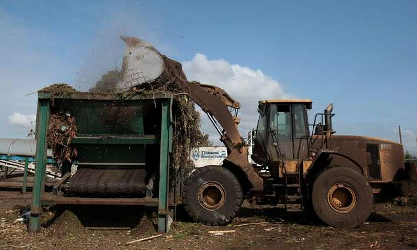 A front-end loader puts residential yard waste and food scraps into a grinder at Cedar Grove's composting facility. The operator of the loader makes sure the mix contains the right amount of green matter and food waste before adding the mixture to the grinder.