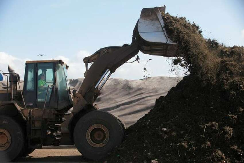 A front-end loader is used to pile ground yard and food waste into rows.