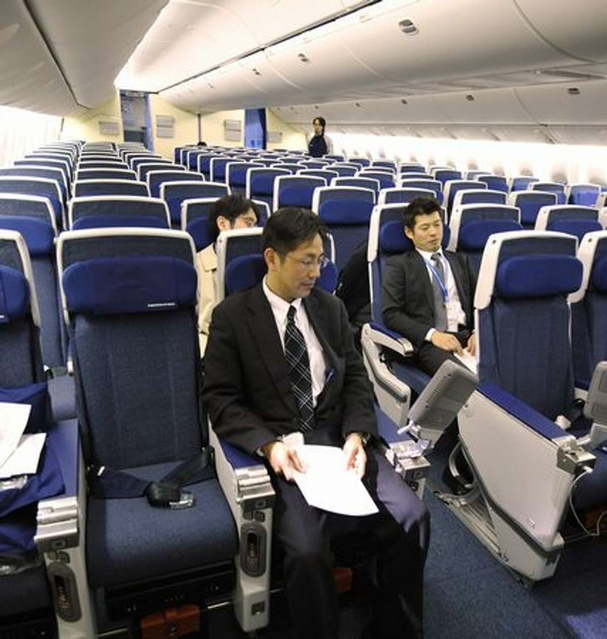Employees of Japan's All Nippon Airways introduce economy-class seats in the company's new Boeing 777-300ER during a press preview at an ANA hangar in Narita International Airport, suburban Tokyo on April 16, 2010. The new aircraft is scheduled to commence flights from April 19 on the Narita-New York route.
