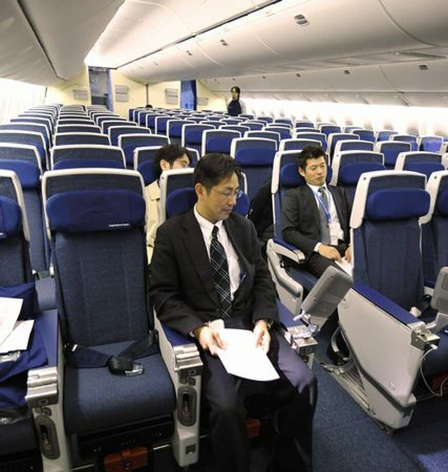 Employees of Japan's All Nippon Airways introduce economy-class seats in the company's new Boeing 777-300ER during a press preview at an ANA hangar in Narita International Airport, suburban Tokyo on April 16, 2010. The new aircraft is scheduled to commence flights from April 19 on the Narita-New York route. Photo: Getty Images