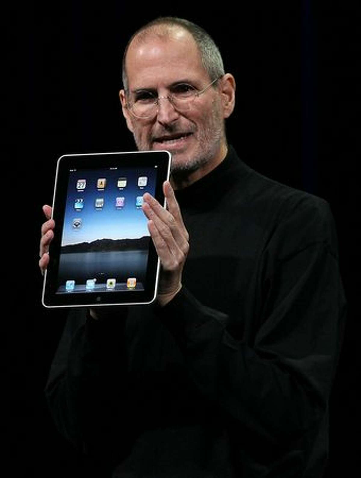 Apple CEO Steve Jobs holds up the new iPad as he speaks during an Apple special event Jan. 27 at the Yerba Buena Center for the Arts in San Francisco. Apple introduced its latest creation, the iPad, a mobile tablet browsing device that is a cross between the iPhone and a MacBook laptop.