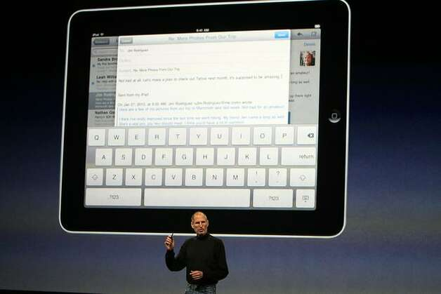 Apple CEO Steve Jobs demonstrates the new iPad as he speaks during an Apple special event Jan. 27 at the Yerba Buena Center for the Arts in San Francisco. Apple introduced its latest creation, the iPad, a mobile tablet browsing device that is a cross between the iPhone and a MacBook laptop. Photo: Getty Images