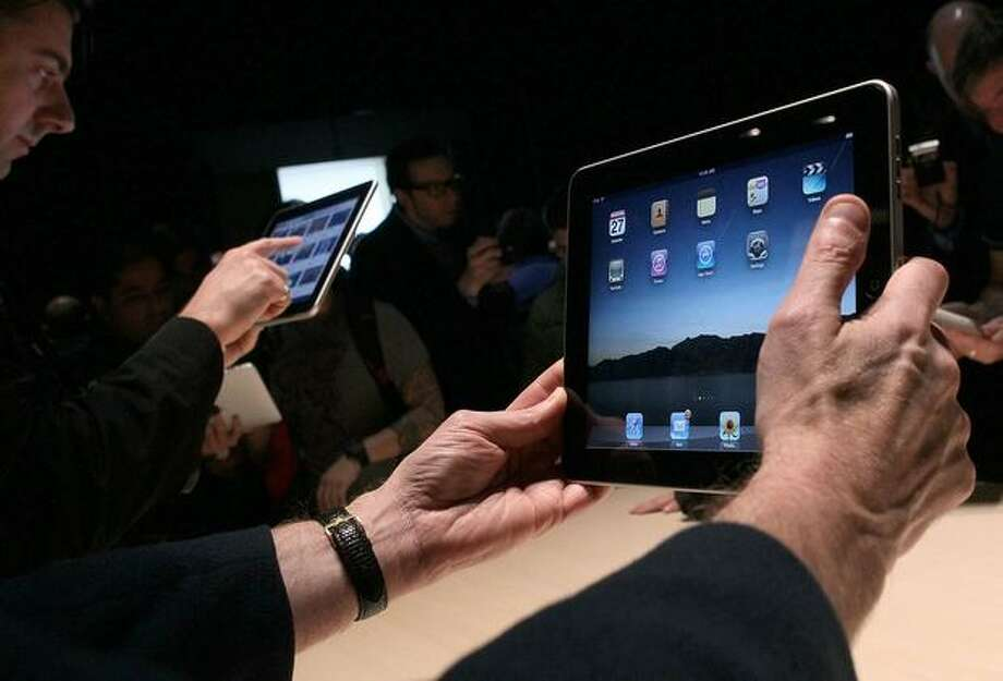 Event guests play with the new Apple iPad during an Apple special event Jan. 27 at the Yerba Buena Center for the Arts in San Francisco. Photo: Getty Images