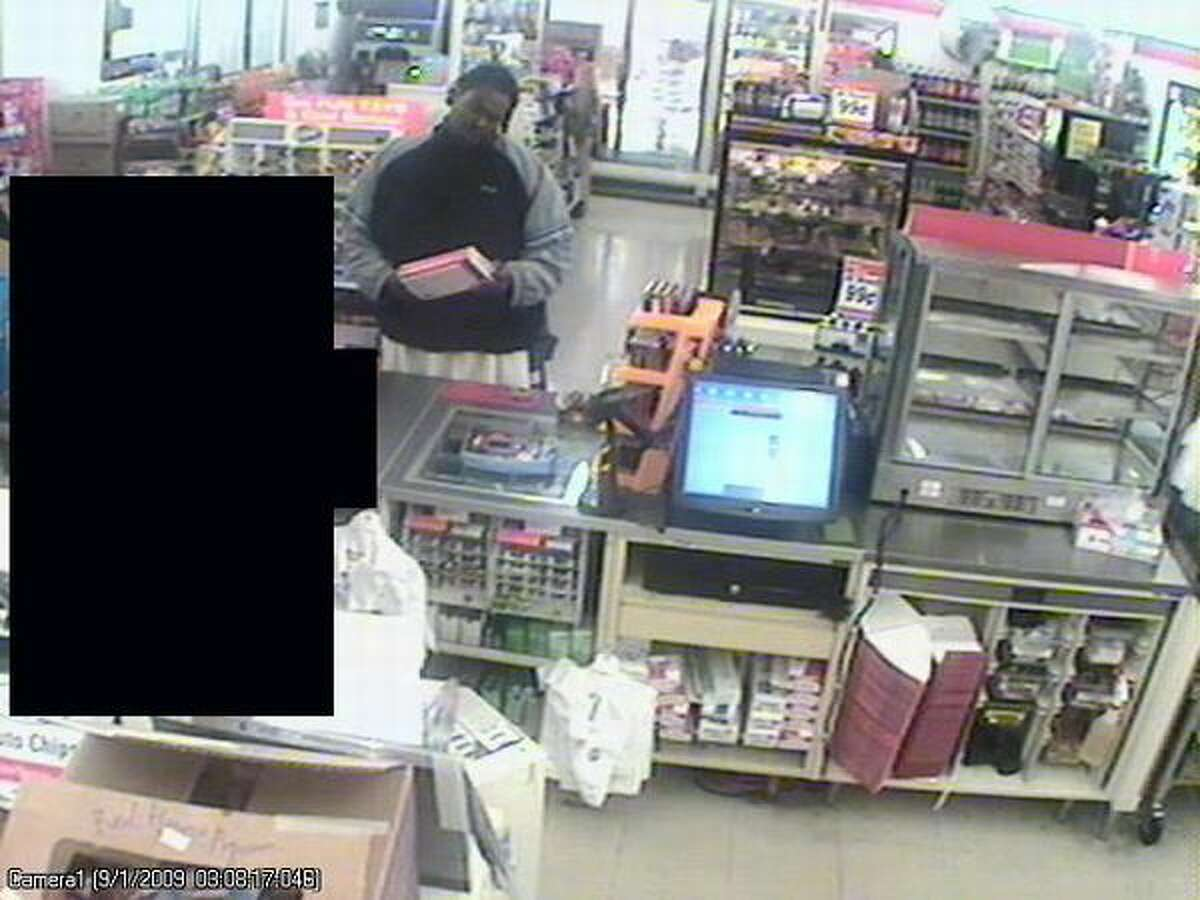 This Sept. 1 surveillance image shows one of the three men police suspect in a string of recent robberies. A clerk is blacked out. (Seattle Police Department photo)