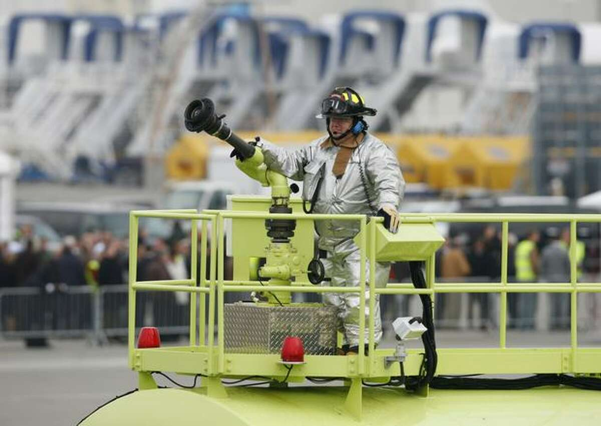 A firefighter waits at the ready for Boeing's new 747-8 to make its first flight at Paine Field in Everett. The flight was delayed for hours because of weather.